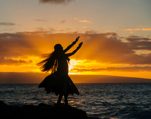 Silhouetted young woman in traditional costume, hula dancing on coastal rock at sunset, Maui, Hawaiiの写真素材 [FYI03527045]