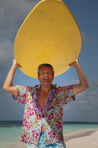 Senior man holding surfboard, portraitの写真素材 [FYI03527112]