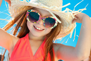 Girl wearing sunglasses and straw hatの写真素材 [FYI03527193]