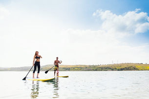 Couple and toddler daughter standup paddleboarding on tranquil sea, Carlsbad, California, USAの写真素材 [FYI03527249]