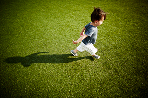 Boy with shadow running across the grassの写真素材 [FYI03527320]