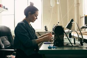 Young female seamstress using sewing machine in fashion studioの写真素材 [FYI03527496]