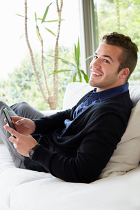 Portrait of man relaxing on sofa with feet up holding digital reading deviceの写真素材 [FYI03527534]