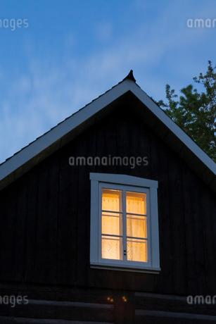 Exterior of log house, room illuminated by light, duskの写真素材 [FYI03527561]