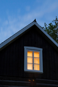 Exterior of log house, room illuminated by light, duskの写真素材 [FYI03527561]