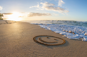 Smiley face, drawn in sand, sunset, Hawaiiの写真素材 [FYI03527638]