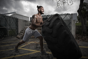 Male boxer with gritted teeth pushing truck tyre in yardの写真素材 [FYI03527718]