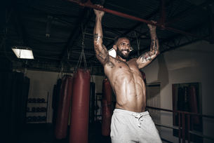 Male boxer doing pull ups with gritted teeth in gymの写真素材 [FYI03527720]