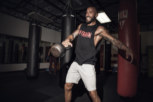 Male boxer lifting kettlebell with gritted teeth in gymの写真素材 [FYI03527726]