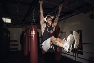 Male boxer training on bar with gritted teeth in gymの写真素材 [FYI03527728]