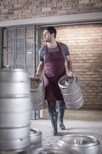 Brewer carrying two kegs of beerの写真素材 [FYI03527756]