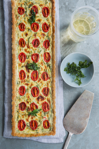 Overhead view of quiche with tomato and herb garnishの写真素材 [FYI03527935]