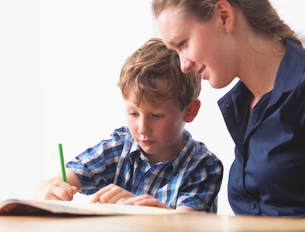 A six year old boy doing his homework with his mum at homeの写真素材 [FYI03528003]