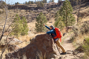 Backpacker pointing up, Smith Rock State Park, Oregonの写真素材 [FYI03528028]