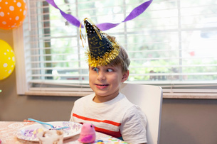 Boy in party hat sitting at table eating birthday cake pulling funny faceの写真素材 [FYI03528041]