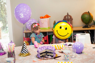 Two girls sitting at birthday party table with cake playing with smiley face balloonの写真素材 [FYI03528043]