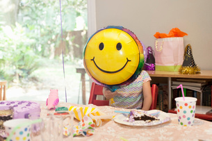 Girl sitting at birthday party table with cake playing with smiley face balloonの写真素材 [FYI03528044]