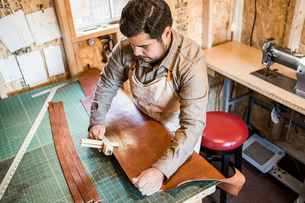 Leather craftsman using wooden clamp on workshop benchの写真素材 [FYI03528066]