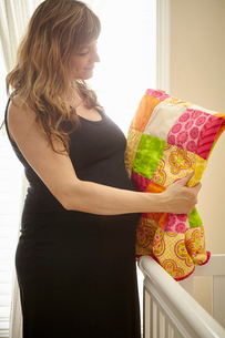 Pregnant woman inspecting homemade quilt in nurseryの写真素材 [FYI03528077]