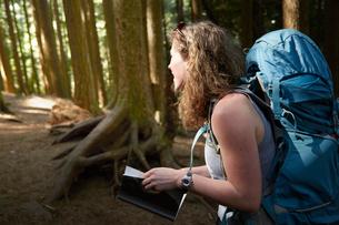 Female backpacker hiking in woodsの写真素材 [FYI03528178]