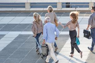 Five adults walking across paving slabsの写真素材 [FYI03528190]
