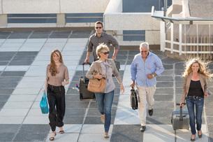 Five adults walking across paving slabsの写真素材 [FYI03528192]
