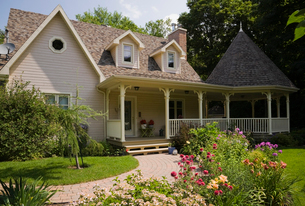 Beige and brown cottage style home with red Monarda flowers in garden at summer, Quebec, Canadaの写真素材 [FYI03528209]