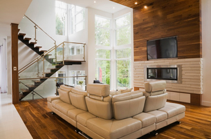 Living room with beige leather sofas and fireplace inside luxurious home, Quebec, Canadaの写真素材 [FYI03528210]