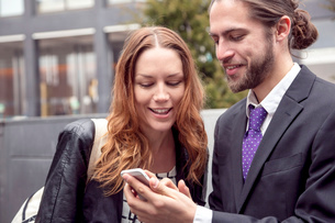 Business people sharing information on smartphone, New York, USAの写真素材 [FYI03528240]