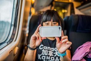 Woman on train using smartphone to take photographの写真素材 [FYI03528372]