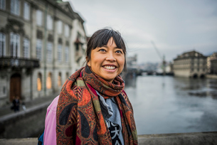 Portrait of mid adult woman in front of river, looking awayの写真素材 [FYI03528376]