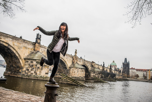 Woman balancing on bollard in front of Charles Bridge, Pragueの写真素材 [FYI03528379]
