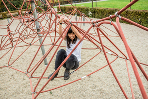 Mid adult woman using climbing ropes, smiling at cameraの写真素材 [FYI03528381]