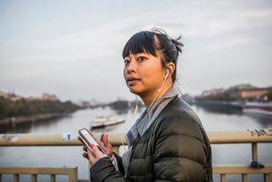 Portrait of woman in front of river wearing earphonesの写真素材 [FYI03528384]