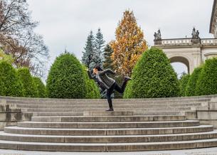 Side view of woman on stone steps posing on one leg, Prague, Czech Republicの写真素材 [FYI03528386]