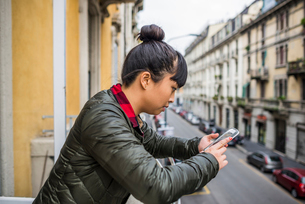 Side view of woman leaning against balcony using smartphone, Milan, Italyの写真素材 [FYI03528388]