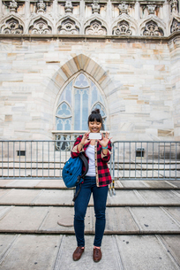 Woman taking selfie in front of Duomo Cathedral, Milan, Italyの写真素材 [FYI03528391]