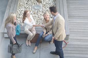 Businessman shaking hands with businesswomen on hotel terraceの写真素材 [FYI03528475]
