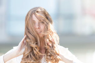 Portrait of beautiful young woman with long red windswept hairの写真素材 [FYI03528541]