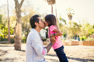 Girl kissing father in community gardenの写真素材 [FYI03528628]
