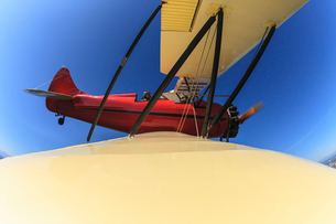 Elevated wide angle view of bi-plane wing and pilot in flightの写真素材 [FYI03528633]