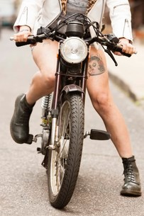 Young woman riding motorcycle along road, low sectionの写真素材 [FYI03528690]