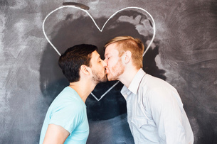 Male couple kissing in front of blackboard with chalk heartの写真素材 [FYI03528700]