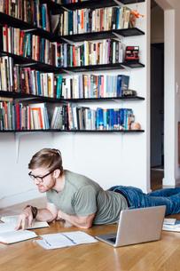 Mid adult man sitting lying on floor, looking through booksの写真素材 [FYI03528753]