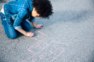High angle view of girl kneeling using chalk to draw hopscotch gameの写真素材 [FYI03528885]