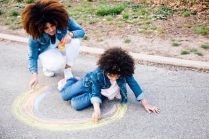 Mother and daughter using chalk to draw colourful circle on pathwayの写真素材 [FYI03528891]