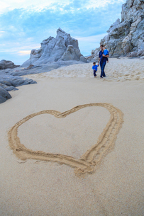 Father and sons walking on beach, heart shape in foregroundの写真素材 [FYI03528926]
