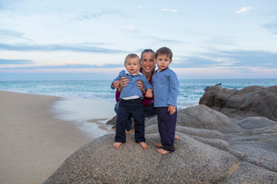 Portrait of mother and sons on rocks on beachの写真素材 [FYI03528931]
