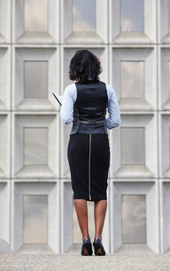 Full length rear view of business woman wearing skirt with zipper running up backの写真素材 [FYI03528985]