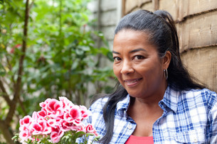 Portrait of mature woman with bunch of pink flowers in gardenの写真素材 [FYI03529051]